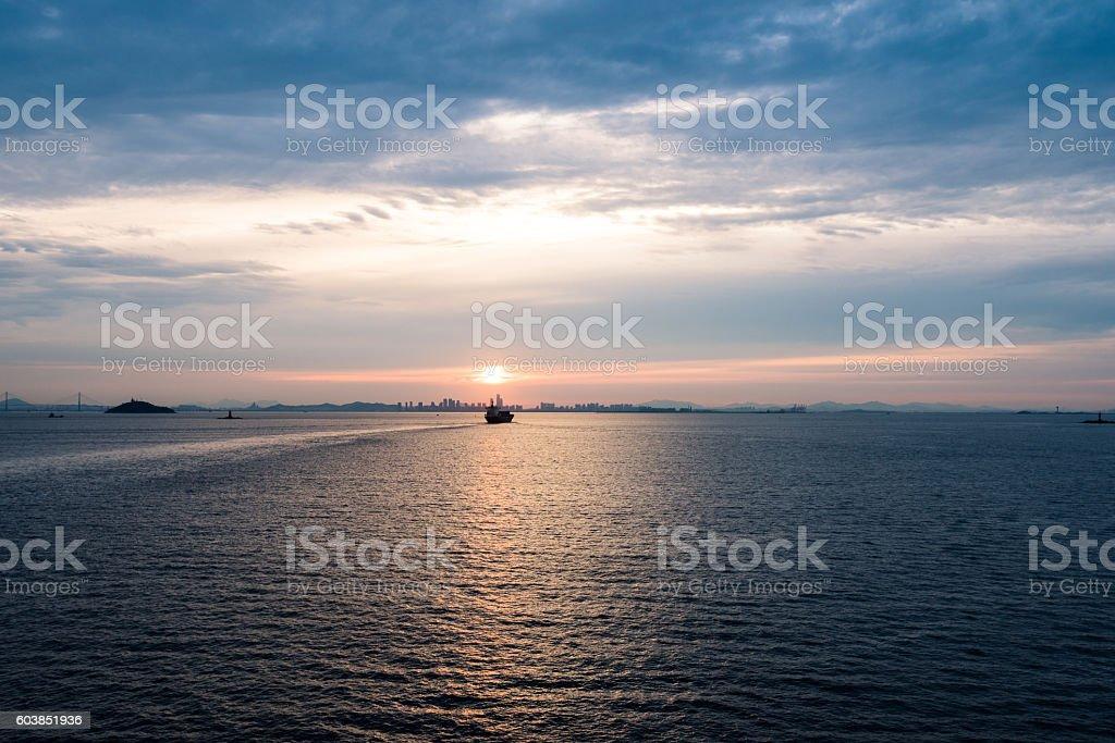 ship moving toward the port at sunrise time stock photo
