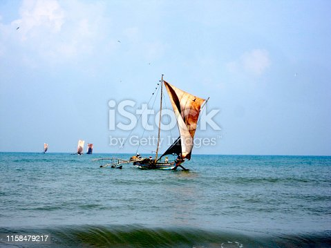 Beautiful wooden ship with leather sails on mast fluttering in wind.