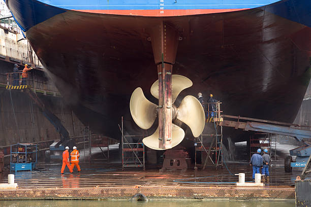 Ship repair Rotterdam, The Netherlands - September 5, 2015: Workers removing algue from the underside of a ship in a repair dry dock. propeller stock pictures, royalty-free photos & images