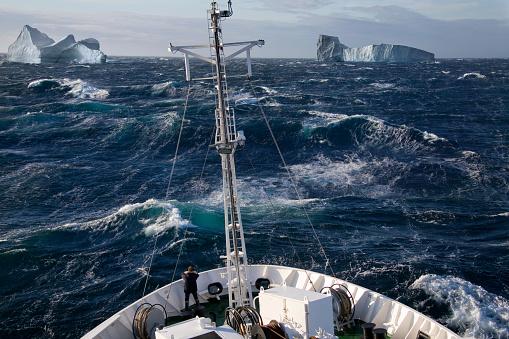 Ship rolling in heavy seas near icebergs in Scoresbysund - Greenland