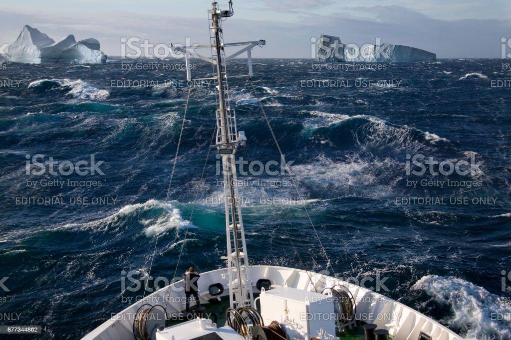 Ship rolling in heavy seas near icebergs in Scoresbysund - Greenland stock photo