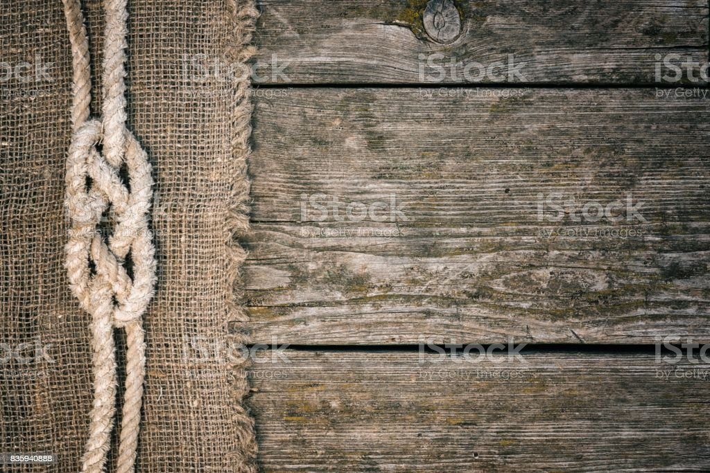 Ship rope on old wood and burlap texture background with copy space stock photo