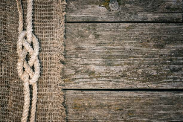 ship rope on old wood and burlap texture background with copy space - vintage nautical stock photos and pictures