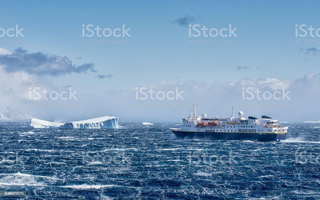 Ship sailing towards an iceberg in Antarctica stock photo