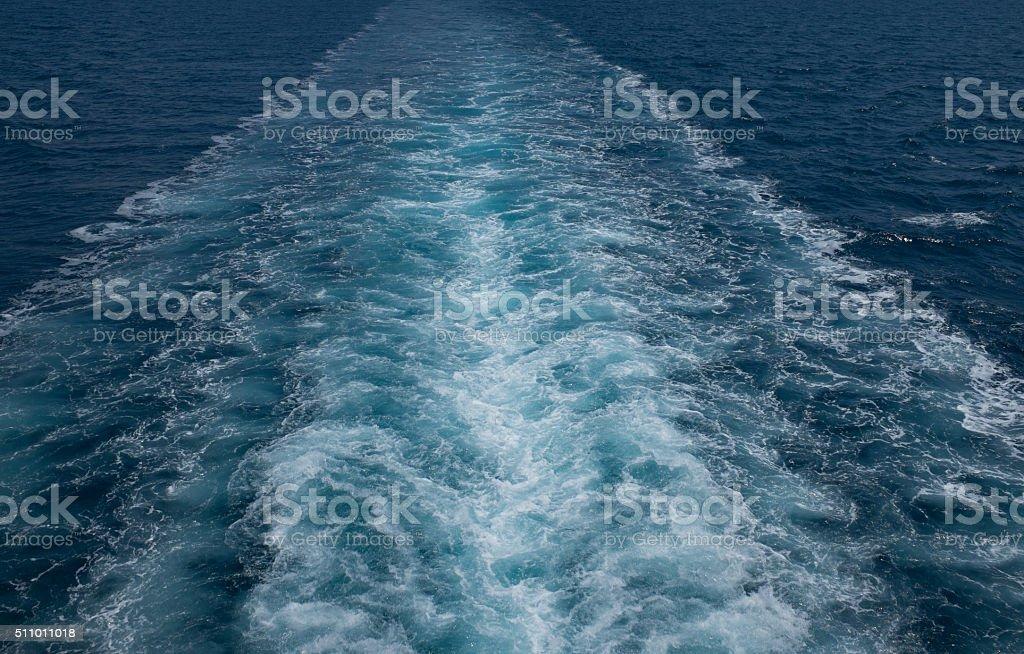 Ship trails in blue sea stock photo