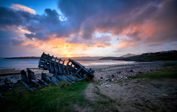 Ship wreck on the beach during a sunrise. stock photo