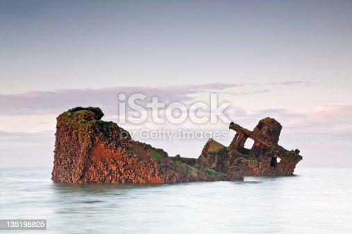 partially sunken shipwreck at sunrise.