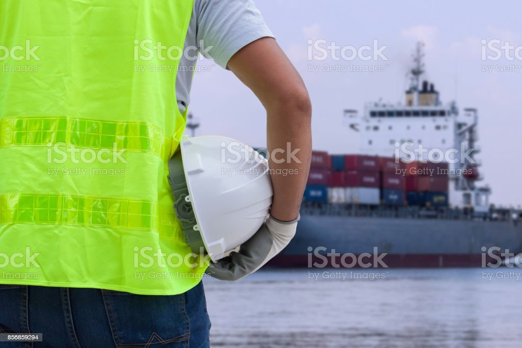 Shipbuilding engineer stands at the dockside in a port. Man is holding a safety helmet, stock photo