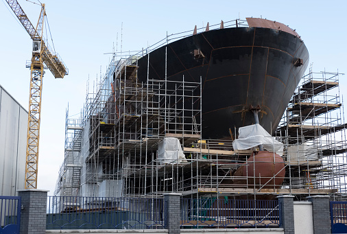 Shipbuilding progress scaffolding and crane large nautical vessel being built at dock port harbour harbour Glasgow traditional industry