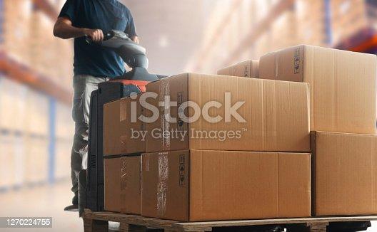 Shipment boxes, Cargo warehouse. Warehouse worker driving electric forklift pallet jack unloading pallet goods.