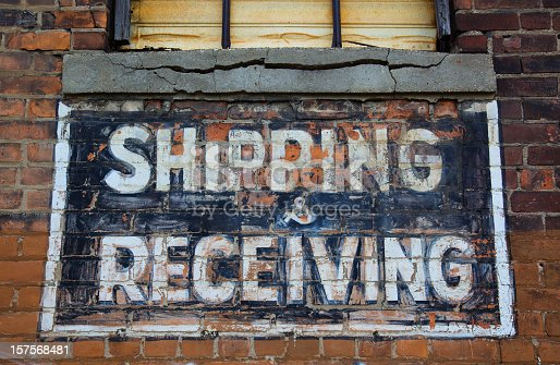 Shipping and receiving painted sign on brick wall of run down warehouse/ factory in downtown Detroit