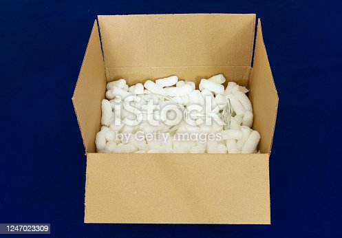 115872043 istock photo Shipping box with glass and packaging peanuts 1247023309