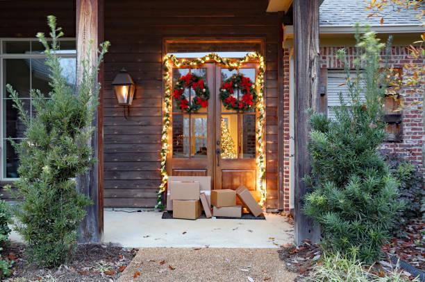 versandschachteln nahe vor der tür während der ferienzeit mit weihnachtsbeleuchtung - buchstabentür kränze stock-fotos und bilder