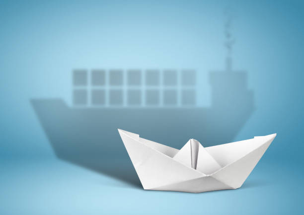 shipping concept, paper boat with container ship shadow, copy cpace stock photo