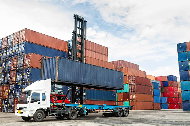 Shipping container being loaded on to a truck for delivery stock photo