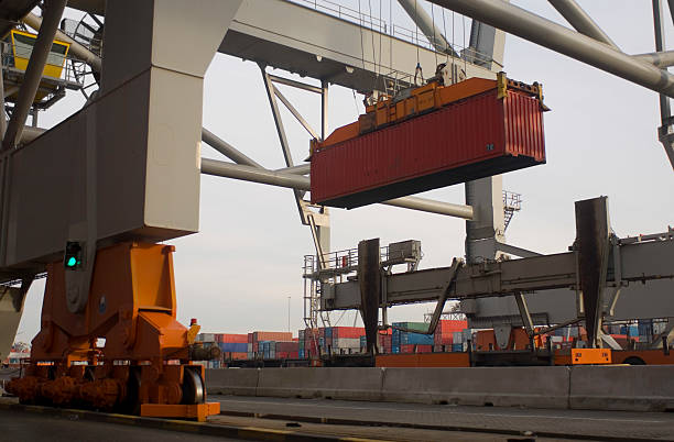 A shipping container being lowered midday in the city stock photo