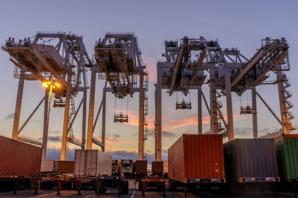 Shipping Container Cranes and Trucks with Sunset Sky in the Port of Oakland. stock photo