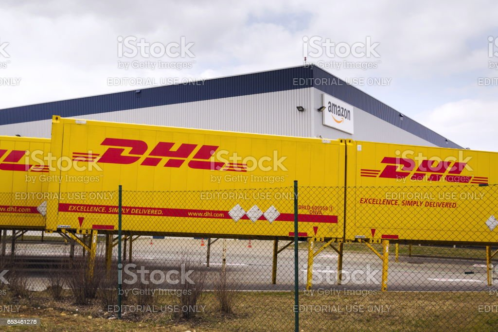 DHL shipping containers in front of Amazon logistics building stock photo