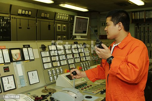 istock Shipping engineer in orange working the controls of machines 146746148