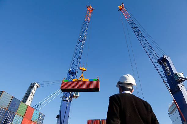 Shipping of containers Lifting a container from stack to a ship. customs official stock pictures, royalty-free photos & images
