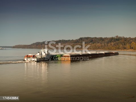 Cargo barge moves by boat