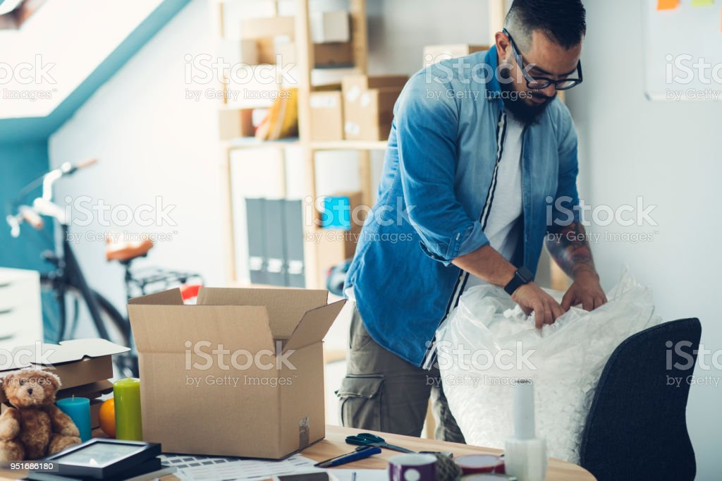 Bearded man packing package. Using packing peanut