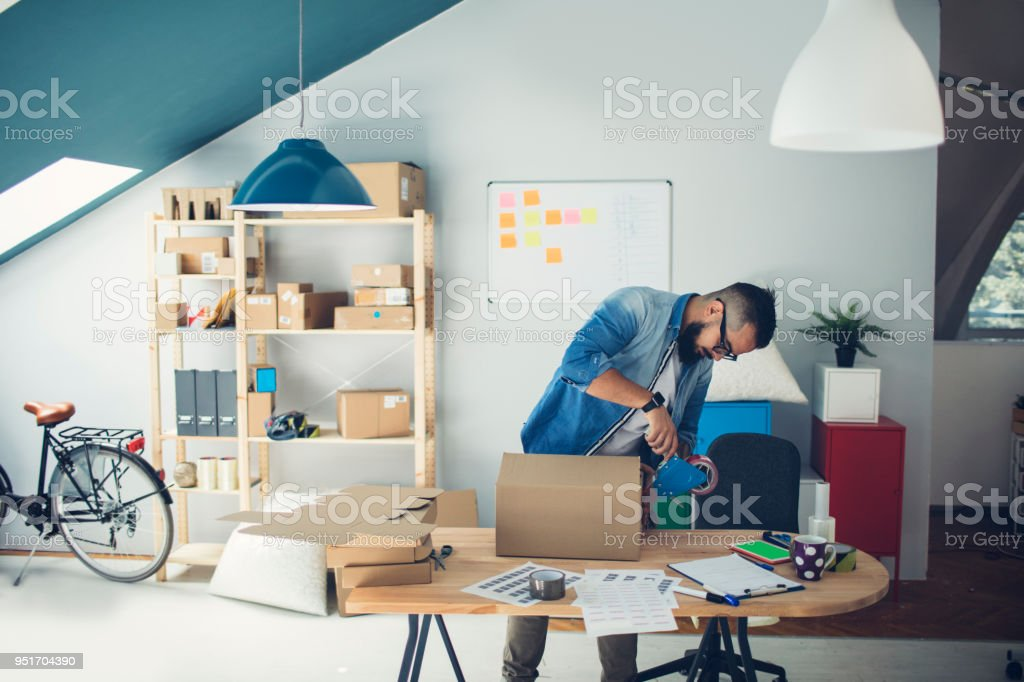 Bearded man packing packages and using adhesive tape.
