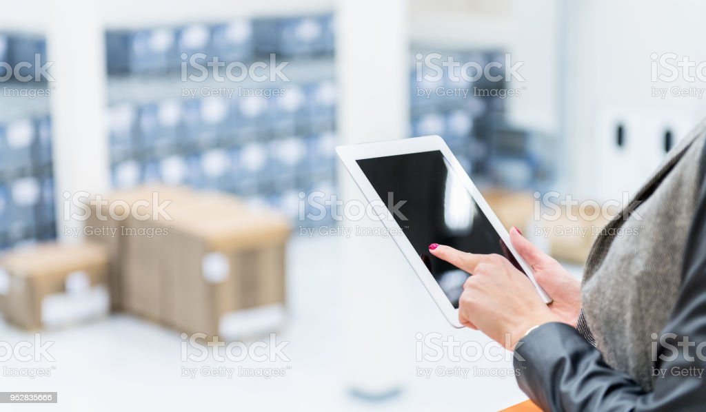 Horizontal color image of female manager using digital tablet and...