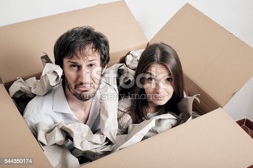 istock Shipping people in a box - puzzled young couple 544350174