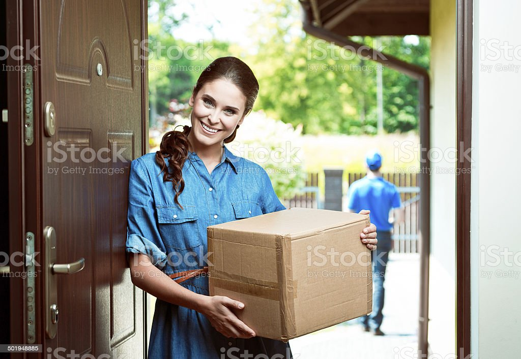 Shipping Young woman standing at the entrance of the house and holding parcel with delivery man in the background. Adult Stock Photo