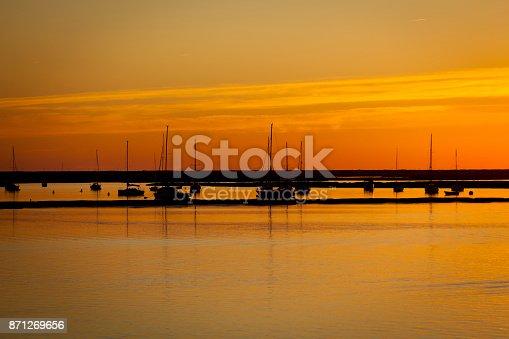 beautiful sunset view of resting ships in the harbor of faro, algarve coastline, portugal.