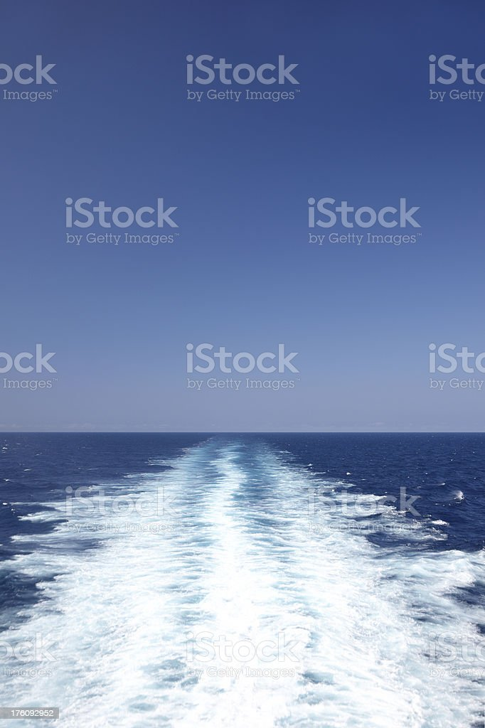 Ships wake in sea to horizon with blue sky royalty-free stock photo