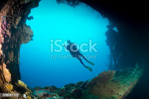 A female diver exploring the wreck Teshio Maru a Japanese Army Cargo Ship with 321 feet (98) on it's length, and was built in 1942-1944. The Teshio is one of the fishiest wrecks in Palau