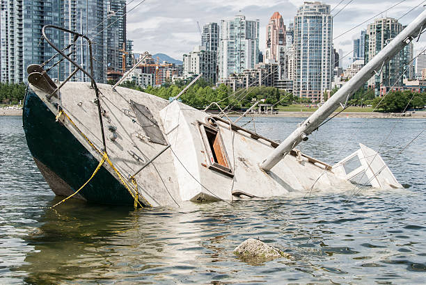 Shipwreck in front of a city Sinking sailboat abandoned on the shore of a city sunken stock pictures, royalty-free photos & images