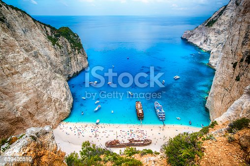 Tourists and tourist boats  in the famous Navagio Bay, Zakynthos island, Greece. The beach of Navagio with the old shipwreck is one of the main tourism spots of Zakynthos island in Greece - beside of the wreck its the turquoise sea what makes this place so famous.