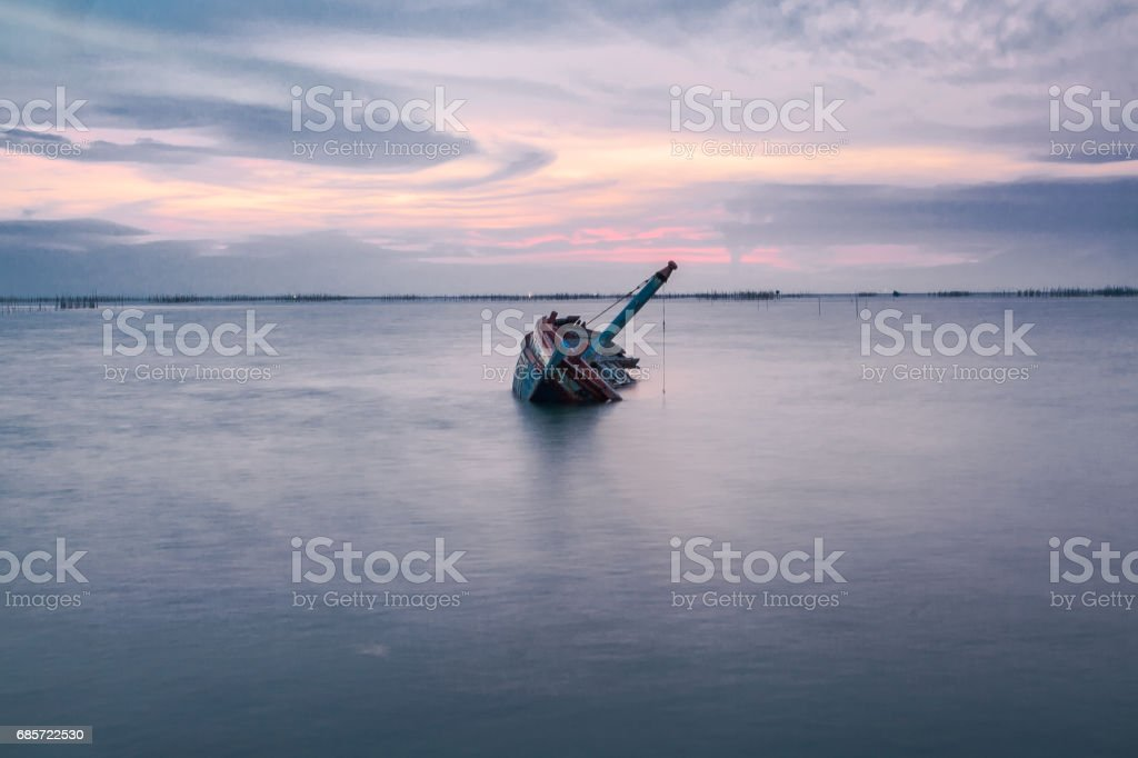 Shipwreck of fish boat at sunset in Thailand. stock photo