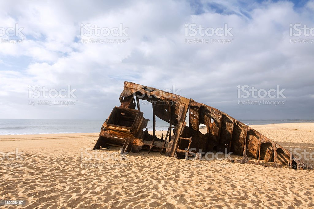 Shipwreck on a beach at sunrise royalty-free stock photo
