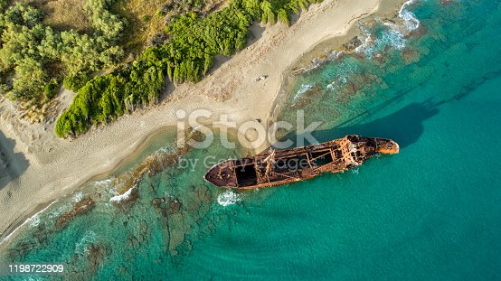 Huge rusty shipwreck stranded on rocks on the long sand beach of south Peloponnese in Greece. Wreck is in very bed condition, exposed to wind and waves.photo taken with drone