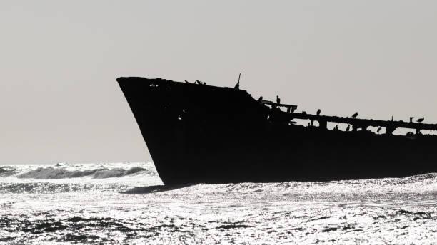 Shipwreck on shore in bright daylight stock photo