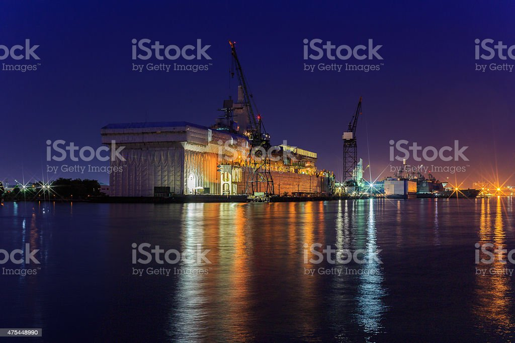 Shipyard repair at night with light reflections in bay stock photo