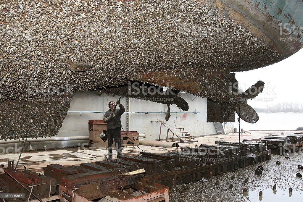 Shipyard worker cleans the ship stuya water stock photo