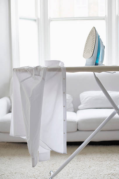 shirt and iron on ironing board - ironing stock photos and pictures