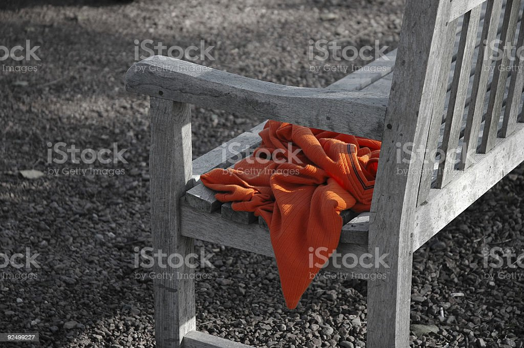 Shirt forgotten on a wooden park bench - color desaturated royalty-free stock photo