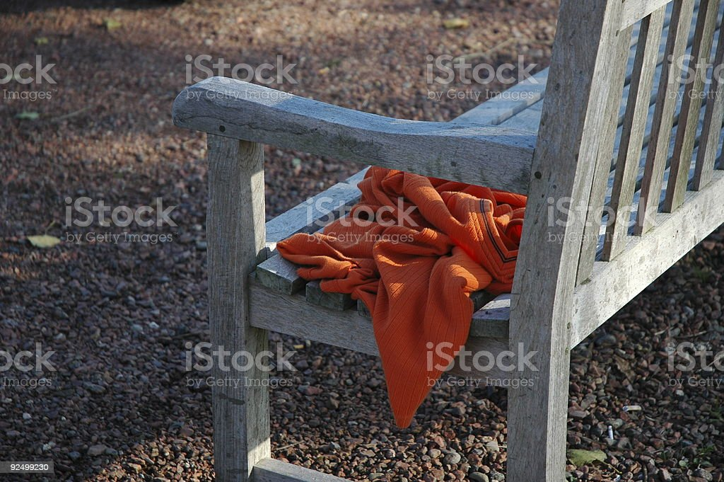 Shirt forgotten on a wooden park bench royalty-free stock photo
