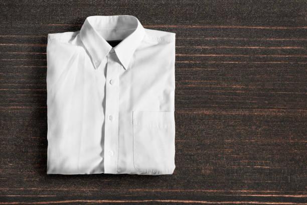 Shirt on wooden background Folded white basic shirt on dark wooden background blouse stock pictures, royalty-free photos & images