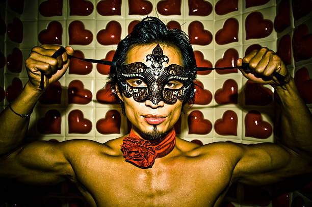 shirtless asian man ties on mask against heart background stock photo