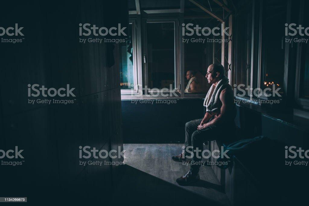 One man, fit shirtless man sitting in dark locker room in gym alone.