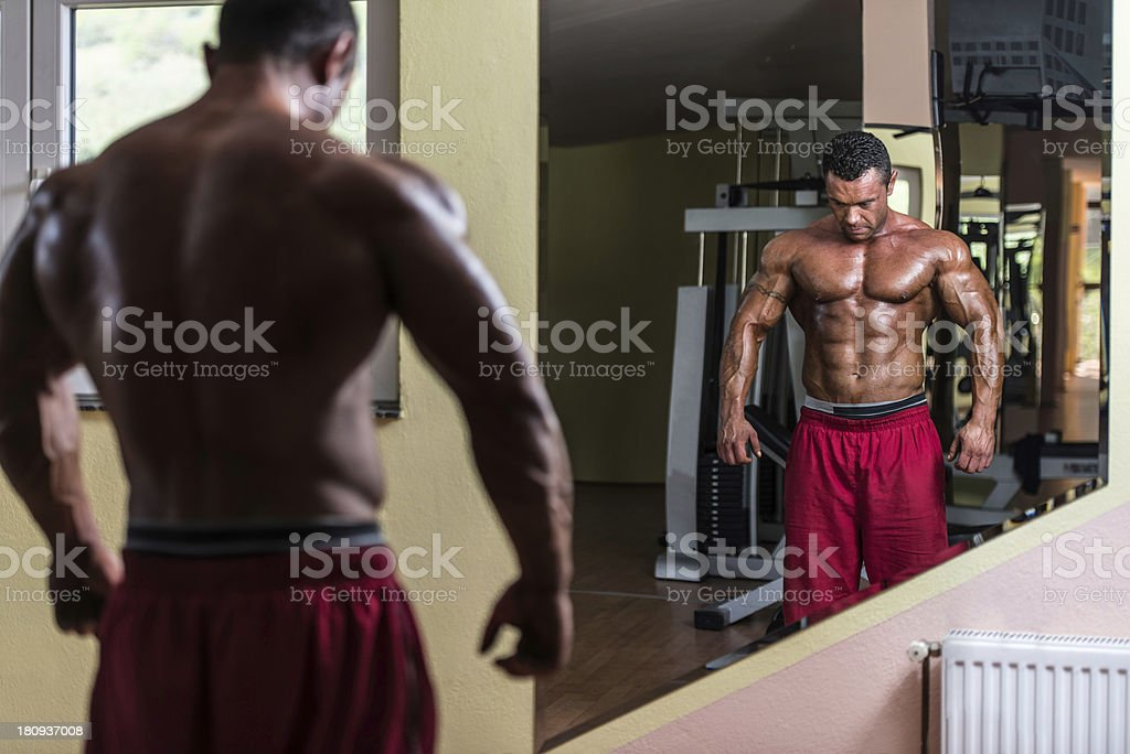 shirtless bodybuilder posing at the mirror royalty-free stock photo