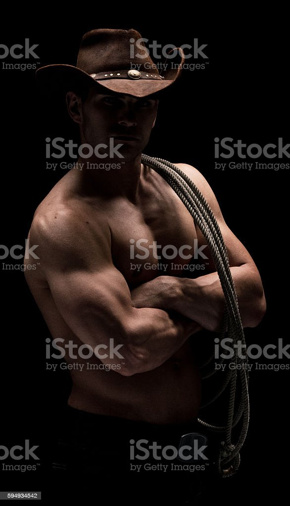 Shirtless cowboy standing with arms crossed – zdjęcie