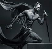 Black and white photo of muscular guy with sword on grey background